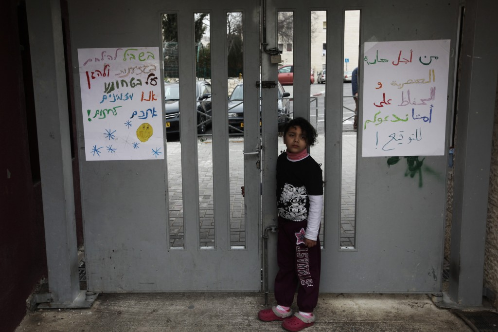"An Arab girl stands near signs against racism at the entrance of the Max Rayne Hand in Hand school for Bilingual education in Jerusalem. In the past two weeks the school has been hit by vandals who have daubed racist threats on its playground walls, including ""Death to Arabs."" (photo credit: Kobi Gideon/Flash90)"