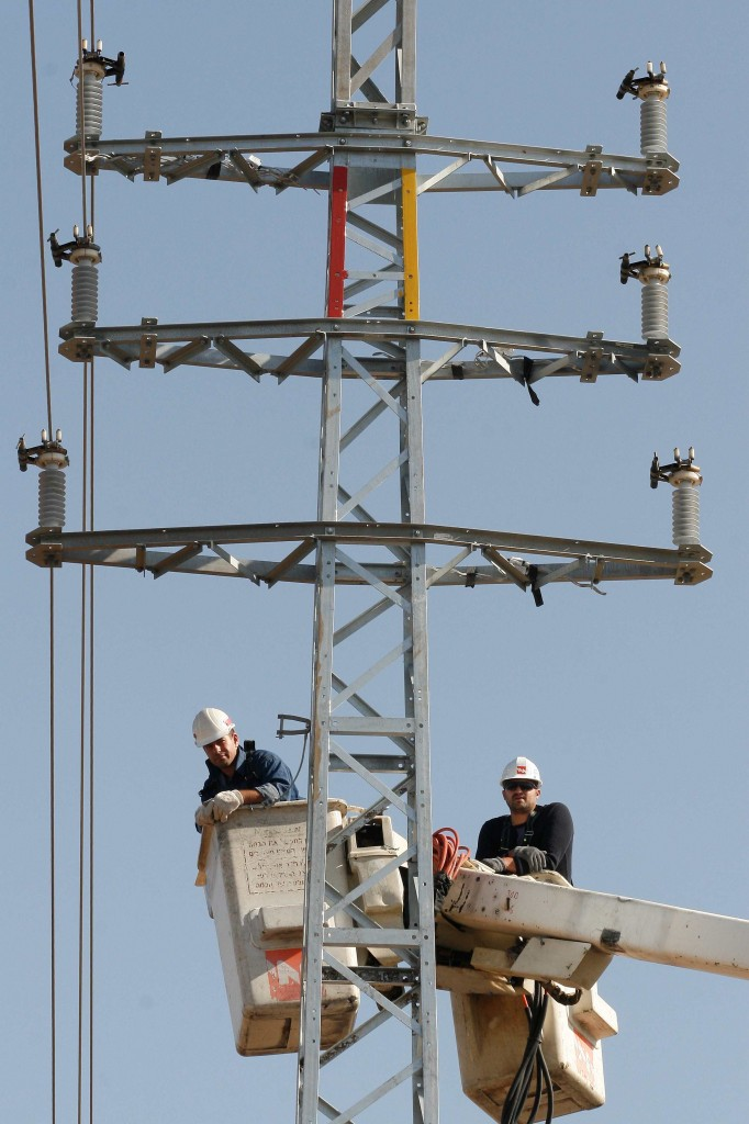A comfortable perch. Israel Electric Company employees (photo credit: Roni Schutzer/Flash 90)
