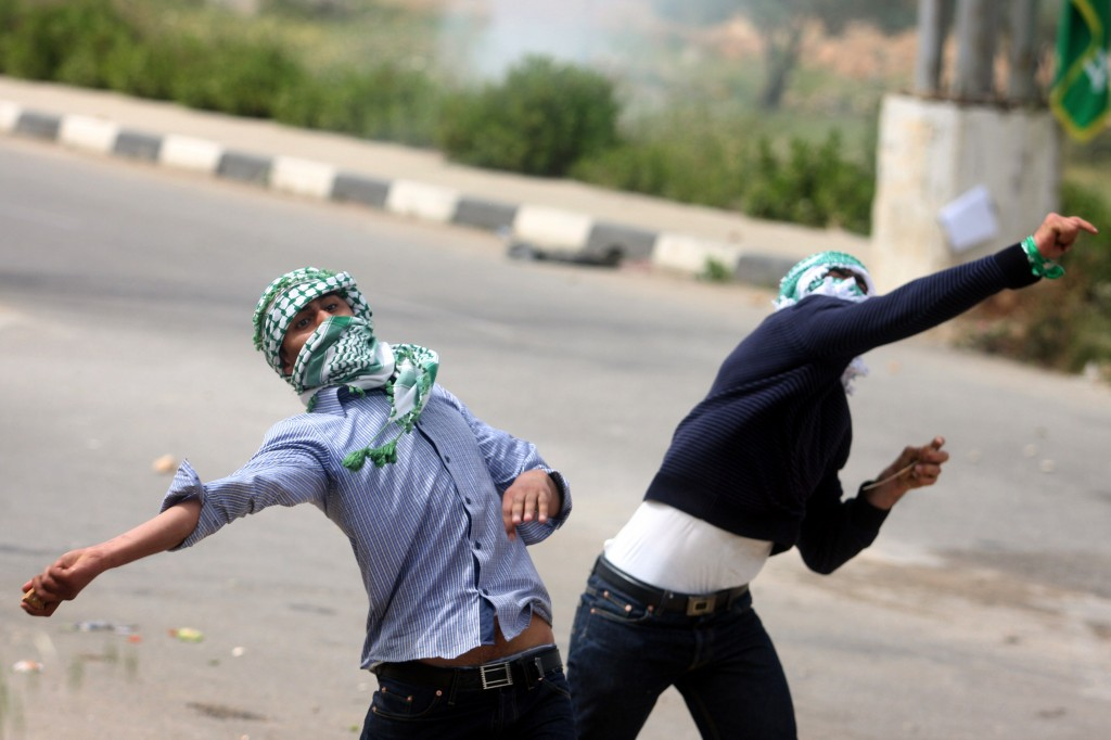 Palestinian protesters throw stones at Israeli troops outside the Ofer military prison near Ramallah (photo credit: Issam Rimawi/Flash90)