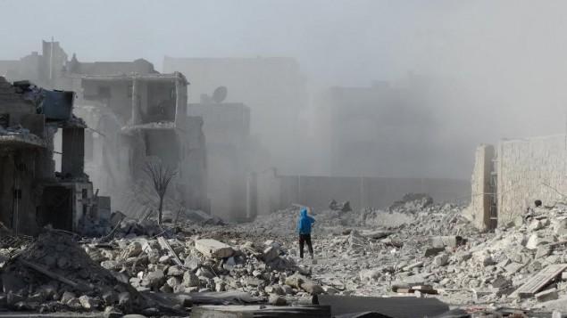 Un homme marche parmi des débris après un bombardement sur la ville d'Alep, le 31 janvier 2014  (Crédit : AFP Mohammed Al-Khatieb)