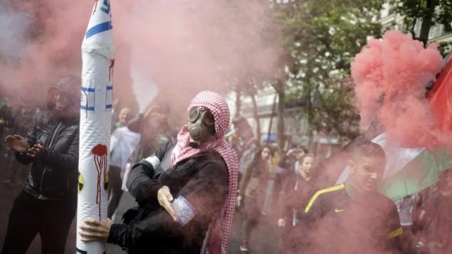 Un manifestant français à Paris qui fait une quenelle en portant un masque et une fausse roquette (Crédit : AFP)