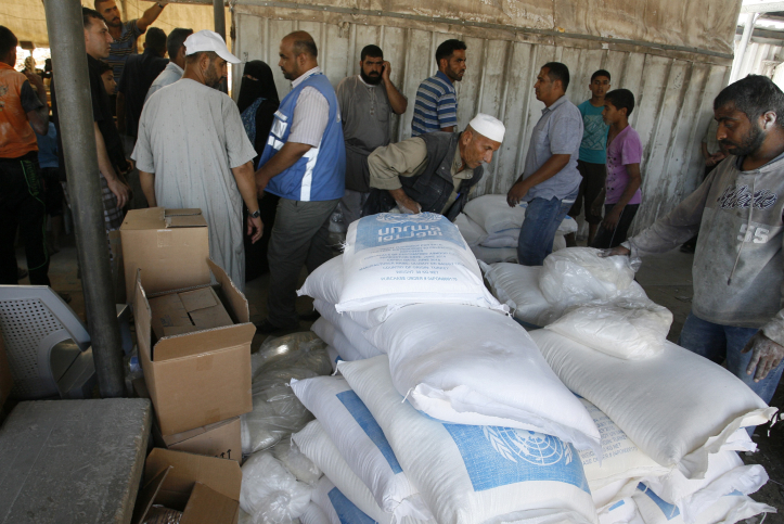Queues of Palestinians getting big white sacks of flour with blue UN logos, Rafah Camp, Gaza Strip.