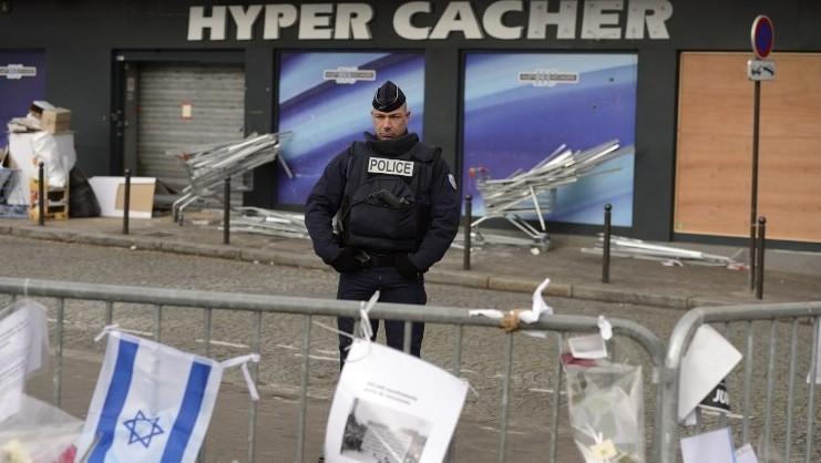 Un policier montant la garde le 21 janvier 2015 devant l'épicerie Hyper Casher où quatre Juifs ont trouvé la mort le 9 janvier 2015 tués par Amédy Coulibaly à Paris (Crédit : AFP/ ERIC FEFERBERG)