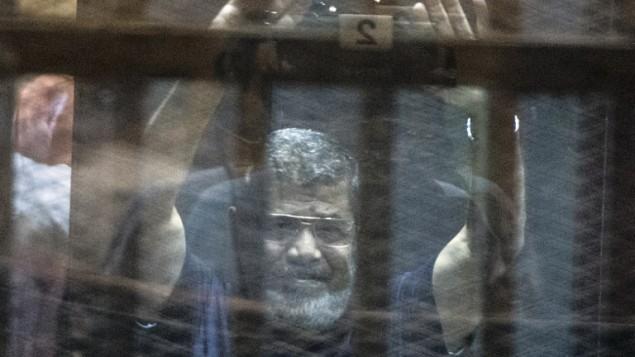 الرئيس المصري المخلوع محمد مرسي وراء قضبان السجن خلال اعلان حكم الاعدام الصادر بحقه وبحق 100 متهم آخرين 16 مايو 2016 AFP/KHALED DESOUKI