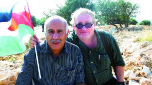 Tuvia, aka Tobi the German, drapes his arm around his friend-for-a-day-or-so, Jibril Rajoub, and waves a Palestinian flag. They are in the village of Bil'in.
