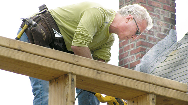A Bonim volunteer works on a two-story house addition for a family with a child who has severe cerebral palsy.