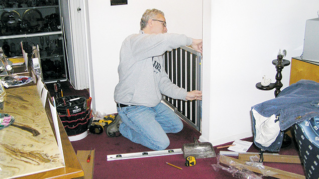 A Bonim volunteer installs a safety gate in an elderly client's house.