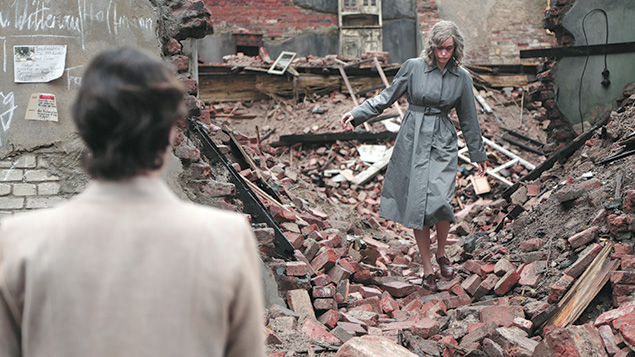 Lene (Nina Kunzendorf) watches as Nelly picks her way through bombed-out rubble. (Schramm Film)