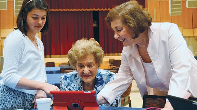 Raina Lambert and Dianne Nashel show Agnes Young, who is active in the Kaplen JCC on the Palisade's Senior Activity Center, how to use an iPad. (JCCTOP)