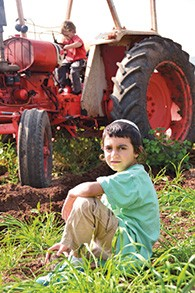 One of Harel Mandel's sons sits by his tractor at Moshav Hazorim.
