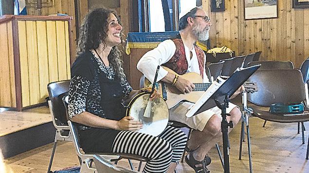 Basya Schechter and Shaul Magid prepare to welcome congregants to an interactive Shabbat service. (Batya Ungar-Sargon)