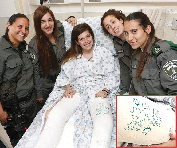 Young Israeli policewomen visit a colleague, a terror victim, and sign her cast. The young woman is a OneFamily client.