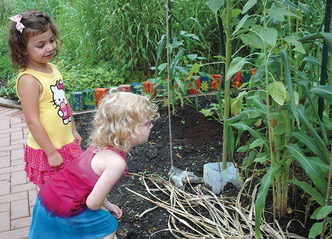 Eliana Abed and Isabel Gross investigate the Three Sisters garden, with its interdependent beans, corn, and squash.