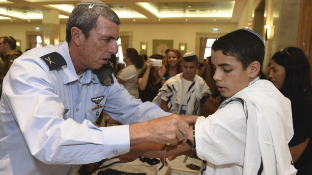 IDF Chief Rabbi Brig. Gen. Rafi Peretz shows Shalom Tiato how to put on his new Tefilin