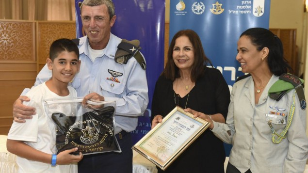 The IDF Chief Rabbi,  IDFWO Chairperson and Col. Yaffa Mor, Head IDF Casualty Department hands Sar Shalom his new Tefilin (Photo: Kobi Koenkas/IDF Widows and Orphans Organication)