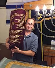 Jerry Schranz holds one of the restored Torah scrolls.