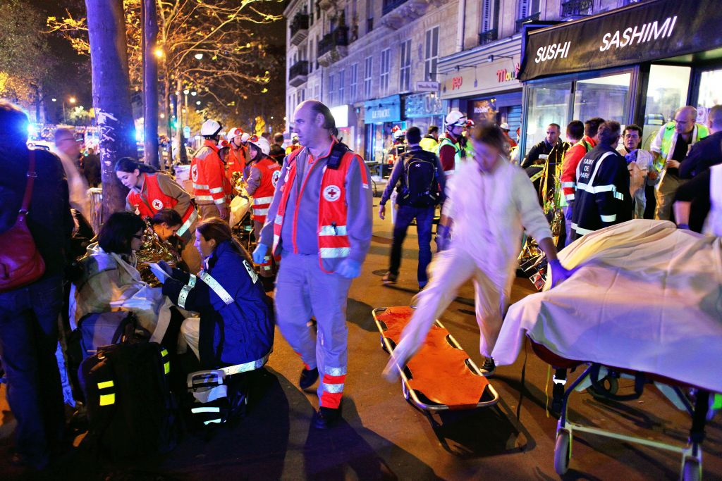 People rest on a bench after being evacuated from the Bataclan theater after a shooting in Paris, Saturday, Nov. 14, 2015. A series of attacks targeting young concert-goers, soccer fans and Parisians enjoying a Friday night out at popular nightspots killed over 100 people in the deadliest violence to strike France since World War II. (AP Photo/Thibault Camus)