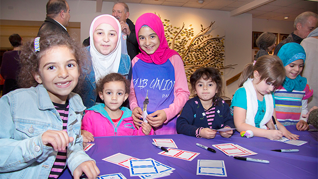 Muslim girls smile as they fill out name tags. (Antony Morales)