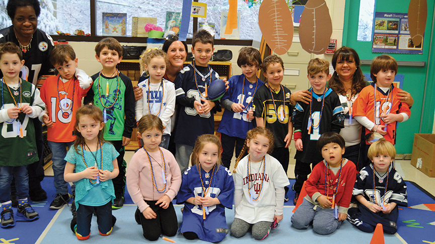 """Tracy's youngest son, Evan (in gold """"50"""" shirt), and his class at the Leonard and Syril Rubin Nursery at the Kaplen JCC, celebrating at a Super Bowl party."""