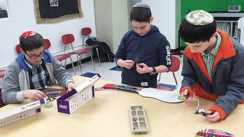 Yavneh students prepare electronic guitars for the MakerXpo.