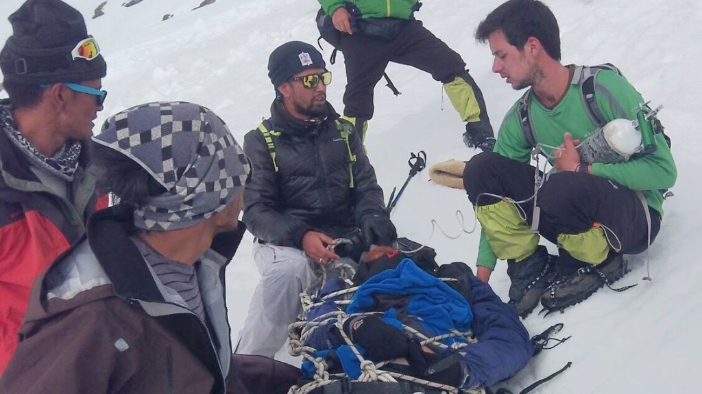 Israeli and Indian climbers giving Sadan first aid in the moments after his fall. (Courtesy Roei Sadan)