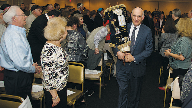 Jeffrey Herrmann, holding the Fair Lawn Jewish Center Holocaust Torah from Pacov, Czechoslovakia, leads a procession of six rescued Holocaust Torah scrolls from Congregation Gesher Shalom in Fort Lee, Barnert Temple in Franklin Lakes, Shomrei Torah in Wayne, Temple Avodat Shalom in River Edge, and Temple Emeth in Teaneck.