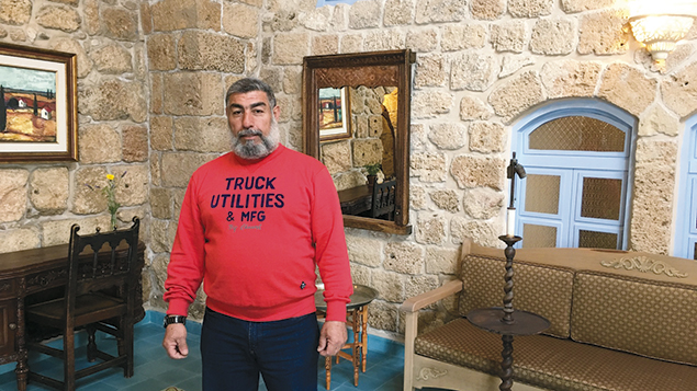 "Muhammad Abu Marwan stands in a guest room in Akko's ""Arabesque: An Arts and Residency Center."" (Orit Arfa)"