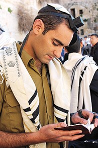 Meir Fox wears an IDF uniform underneath his tallit.