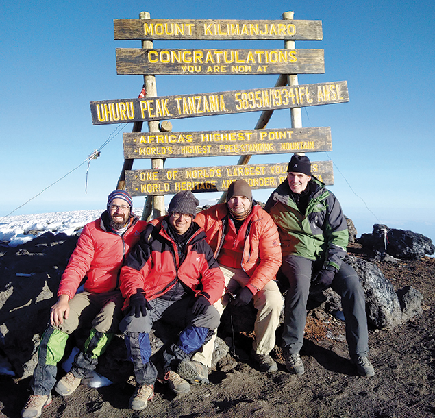 The  climbers smile in victory after reaching Kilimanjaro's summit.