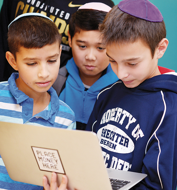Caleb Wolin, Danny Rappaport, and Eli Zaretsky look at a laptop.