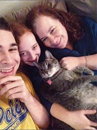 Kyle, Sari, and Adyna Rosen cuddle their cat, Mischief.