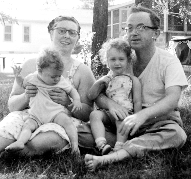 Gitl sits on her mother's lap and Rukhl is on her father's, in 1959.