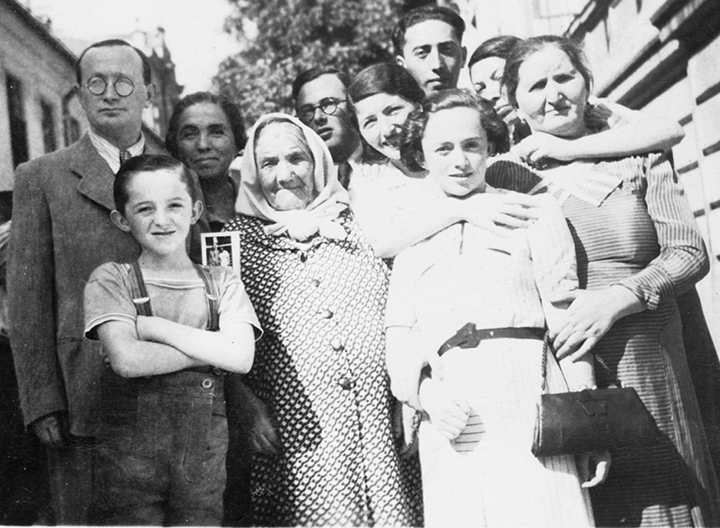 In Czernowitz, Mordkhe Schaechter, with his arms crossed, stands in front of his parents.
