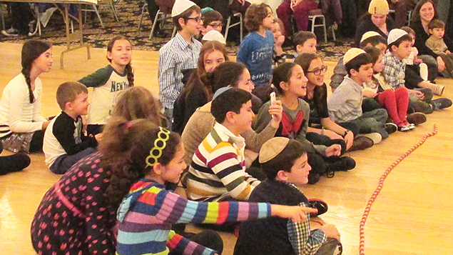 Children at Shaarey Israel's Hebrew school and some parents sit together.