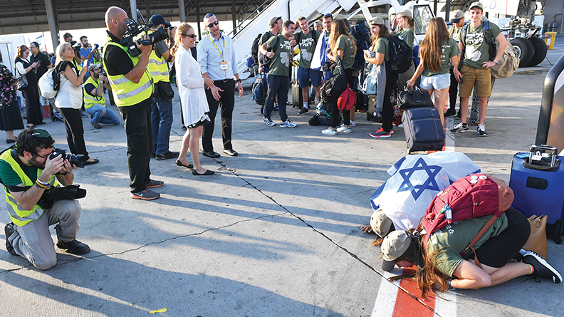 New immigrants kiss the ground as they get off the plane. They're about to join the Israel Defense Forces.