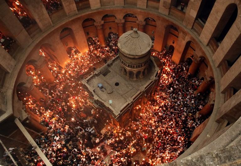 Des fidèles chrétiens orthodoxes allument des bougies dans l'église du Saint-Sépulcre de la Vieille Ville de Jérusalem, pendant la Pâque orthodoxe, le 30 avril 2016. (Crédit : AFP/Thomas Coex)