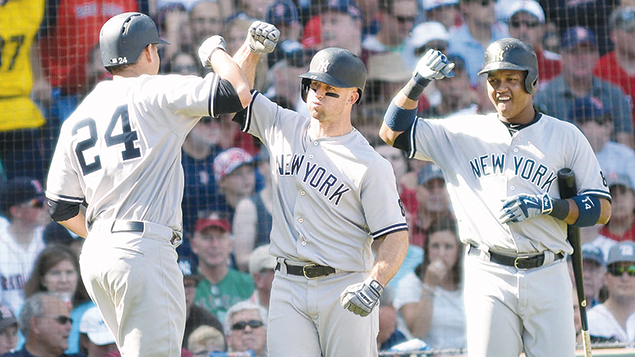 Gary Sanchez, left, high-fiving teammates Brett Gardner, center, and Starlin Castro at a game against the Red Sox at Fenway Park in Boston on September 17. (Darren McCollester/Getty Images)