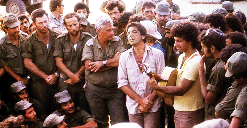 Leonard Cohen entertains Israeli troops on the southern front during the 1973 war with Egypt and Syria as Gen. Ariel Sharon listens appreciatively.