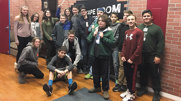 Students tackle a problem-solving exercise on a field trip to an escape room.