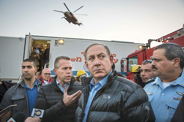 Prime Minister Benjamin Netanyahu confers with fire officials in Zichron Yaakov. (Emil Salman/Pool)
