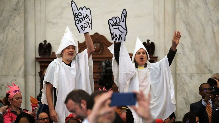 Protesters wearing white sheets shout at Sen. Jeff Sessions (R-AL) as he arrives for his confirmation hearing to be the US attorney general on January 10, 2017 in Washington, DC.   (Somodevilla/Getty Images/AFP)
