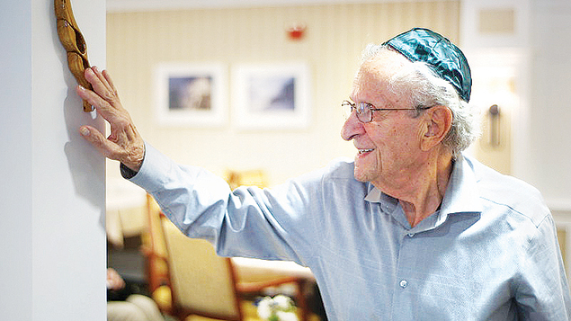 JHAL resident Arnold Klein attaches a mezuzzah to the entrance.