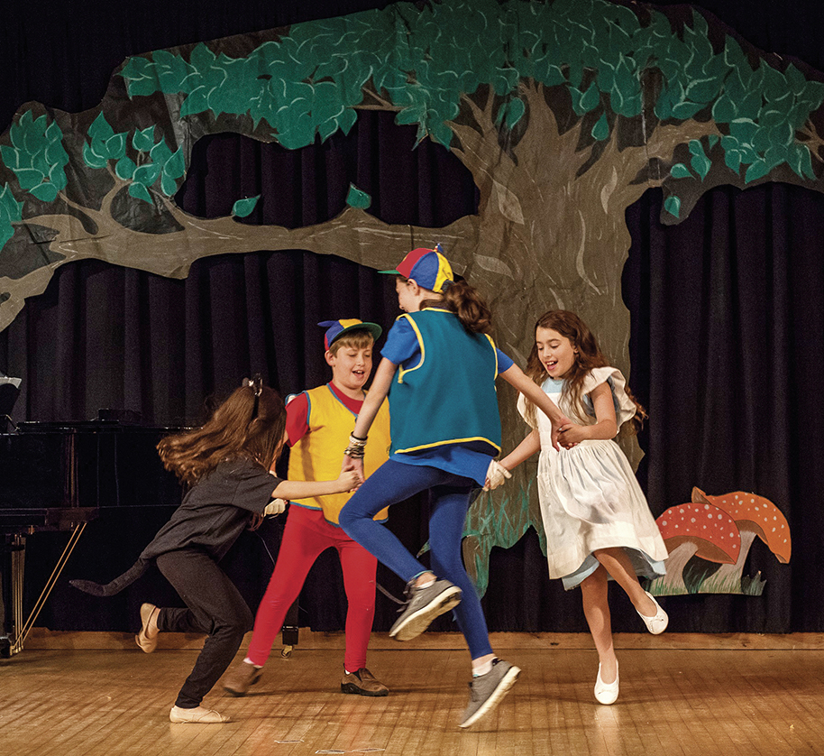 Tweedle Dum (A.J. Horowitz), Alice (Neta Segal), Tweedle Dee (Avia Paz), and Dinah the kitten (Ella Baraket) dance onstage at the JCC.