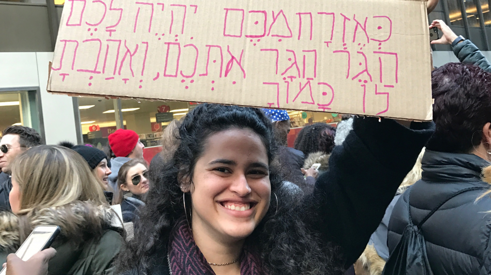 "Hadar Harani, an Israeli shlichit, holds a sign with the quote: ""Strangers who live among you, you shall treat as citizens, and you shall love them as yourselves."" Courtesy of Rabbi Heidi Hoover"