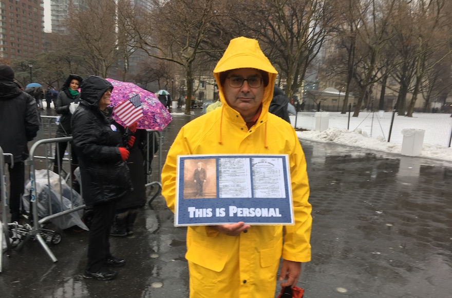Harold Levine brought a poster to the New York City rally showing his grandfather, who immigrated to the United States over 100 years ago, fleeing anti-Semitism in his native Poland. (Josefin Dolsten)