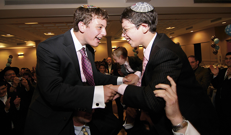 Jacob and his brother Elie celebrate at Jacob's bar mitzvah party.