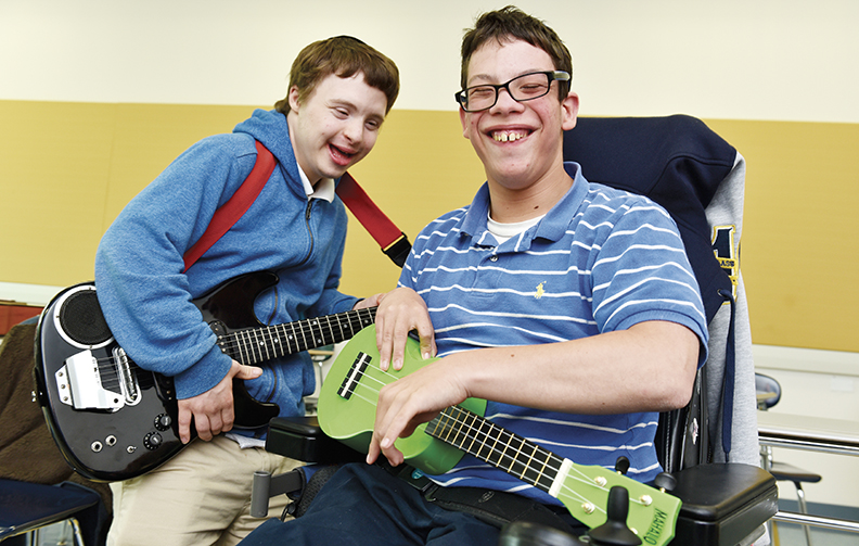 Jacob, right, and another Sinai student benefit from music therapy.