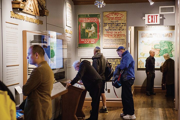 Visitors look at the permanent exhibit, which includes interactive elements.