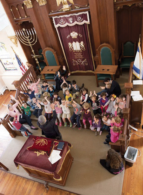 Rabbi Robert Scheinberg and a preschool class are in the sanctuary of the United Synagogue of Hoboken.