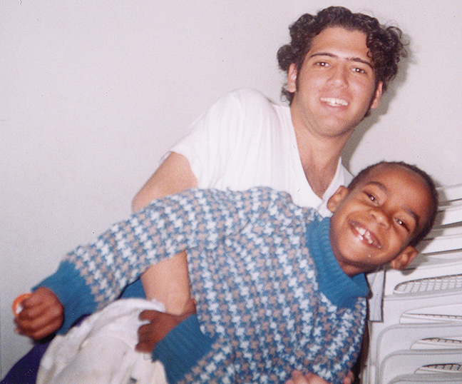 A young Michael Cohen with an even younger Ethiopian-Israeli child.